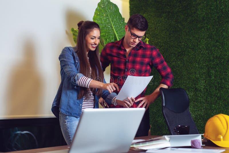 Homem novo e arquitetos fêmeas que trabalham em um projeto junto - Imagem imagens de stock royalty free