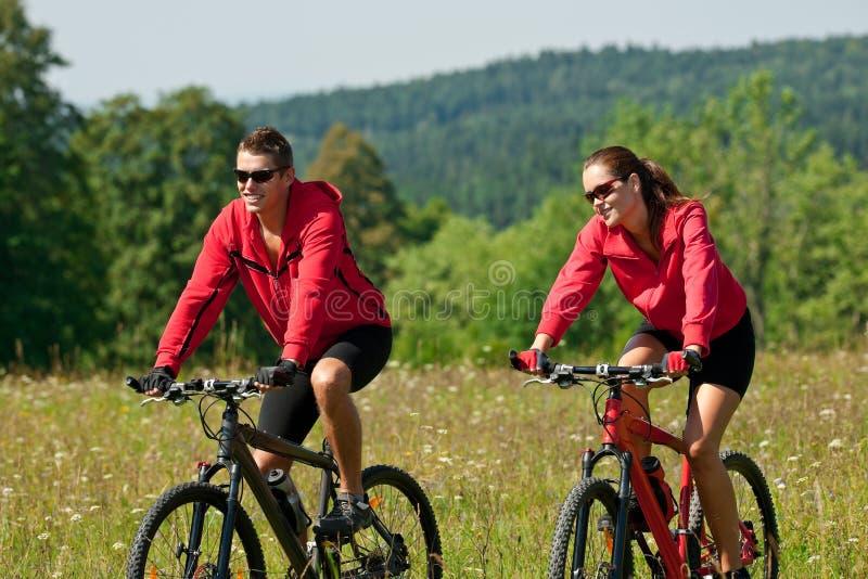 Homem novo e bicicleta de montanha da equitação da mulher imagens de stock