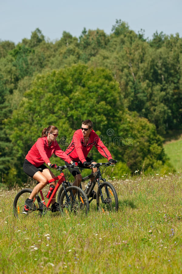 Homem novo e bicicletas de montanha da equitação da mulher imagens de stock