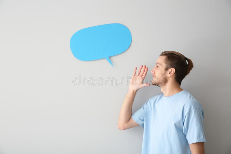 Homem novo e bolha vazia do discurso no fundo claro imagem de stock royalty free
