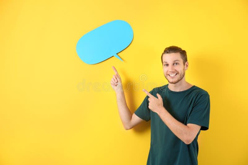 Homem novo e bolha vazia do discurso no fundo da cor imagem de stock