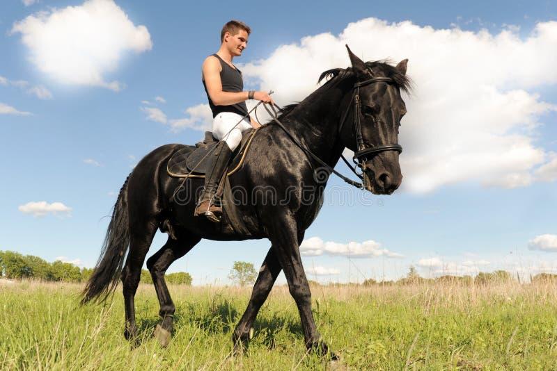 Homem novo e cavalo imagens de stock
