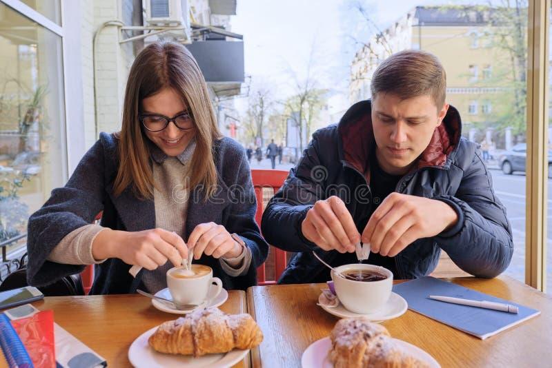 Homem novo e estudantes f?meas dos amigos que sentam-se no caf? exterior, falando, caf? bebendo, ch?, comendo croissant Na tabela fotografia de stock royalty free
