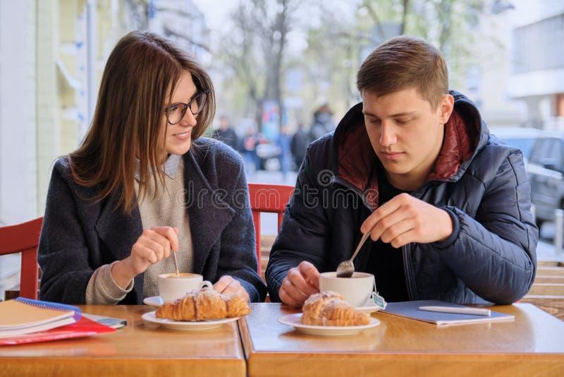 Homem novo e estudantes f?meas dos amigos que sentam-se no caf? exterior, falando, caf? bebendo, ch?, comendo croissant Na tabela fotografia de stock