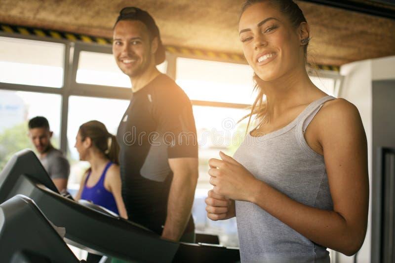 Homem novo e exercício das mulheres no gym fotografia de stock royalty free