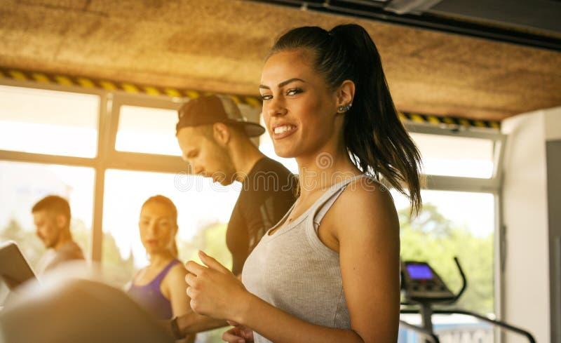Homem novo e exercício das mulheres no gym fotos de stock royalty free