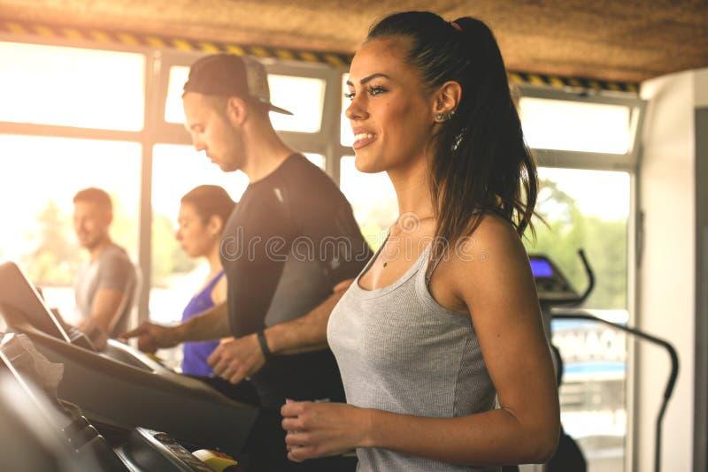 Homem novo e exercício das mulheres no gym fotografia de stock