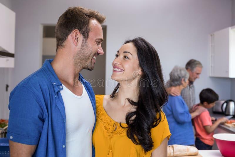 Homem novo e jovem mulher que estão na cozinha foto de stock royalty free
