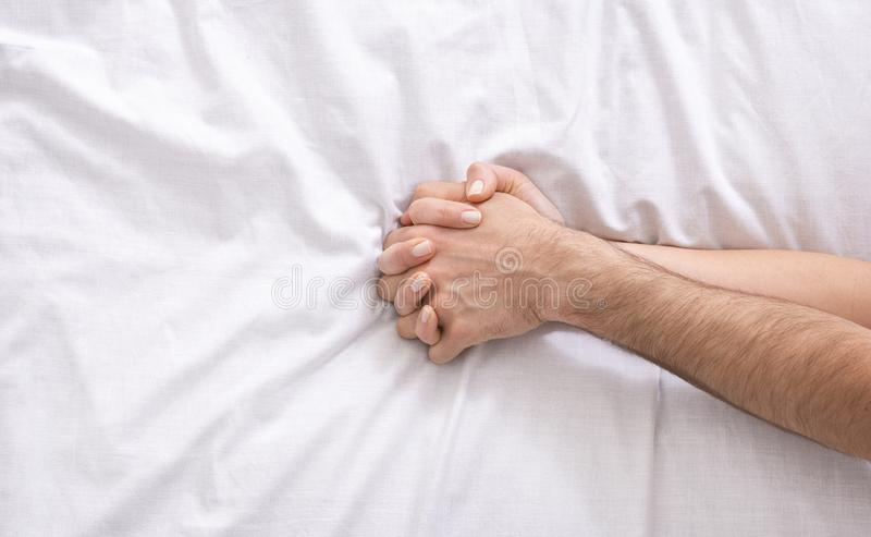 Homem novo e mãos fêmeas na cama, close up fotos de stock