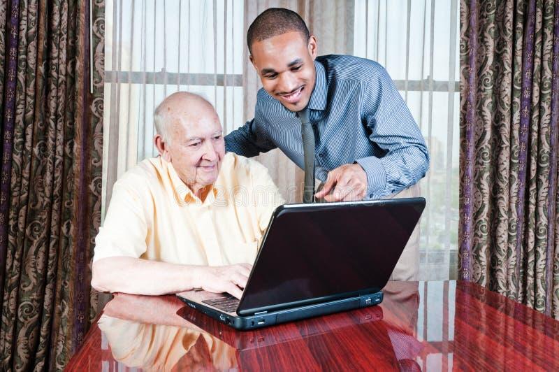 Homem novo e macho sênior que trabalham no computador imagem de stock royalty free