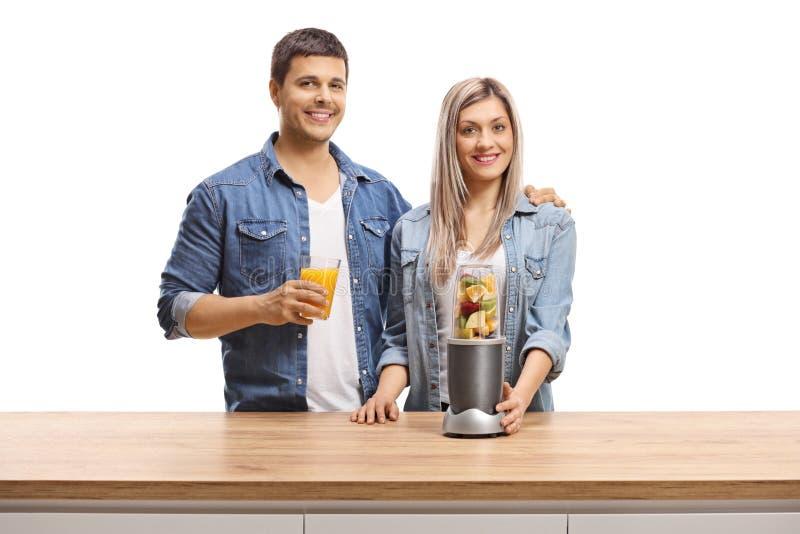 Homem novo e mulher com frutos em um misturador e em um vidro do suco que sorriem na câmera fotografia de stock royalty free