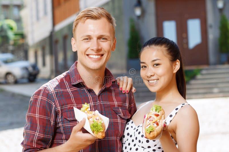 Homem novo e mulher com os hotdogs na rua fotografia de stock royalty free
