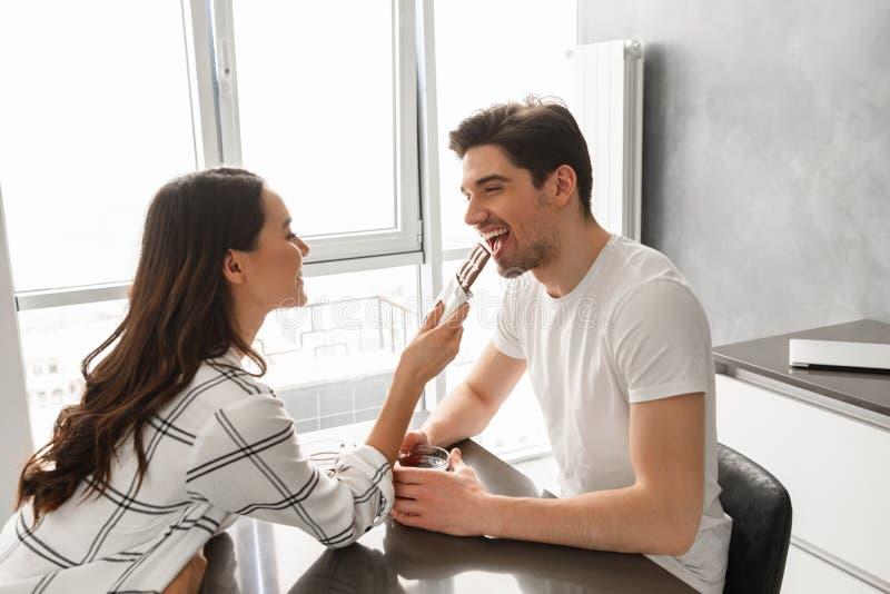Homem novo e mulher dos pares que comem o chocolate e que bebem o chá, wh imagem de stock