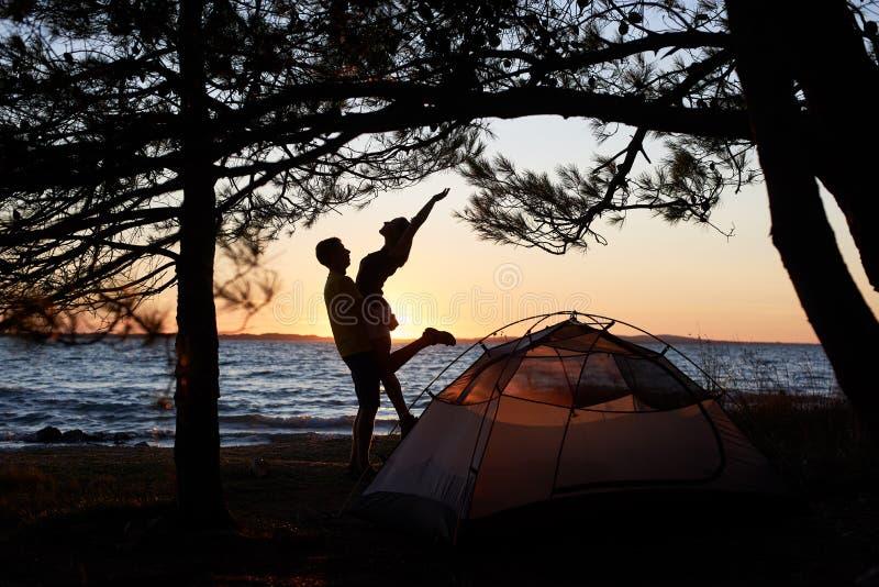 Homem novo e mulher dos pares que têm o resto na barraca do turista e em fogueira ardente na costa de mar perto da floresta fotos de stock royalty free