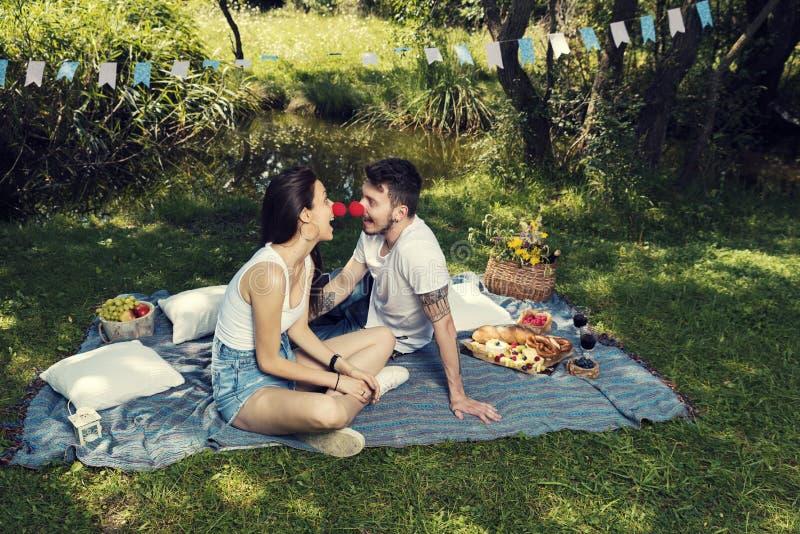 Homem novo e mulher em um piquenique em um parque que senta-se em uma cobertura que beijam-se com os narizes vermelhos do palhaço imagens de stock royalty free