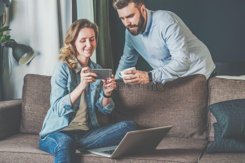 Homem novo e mulher farpados que sentam-se em casa no sofá e que olham a tela do portátil nas mãos dos homens fotografia de stock