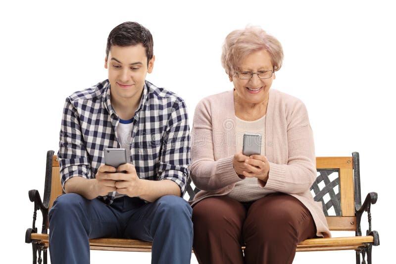 Homem novo e mulher idosa no banco que olha telefones fotografia de stock royalty free