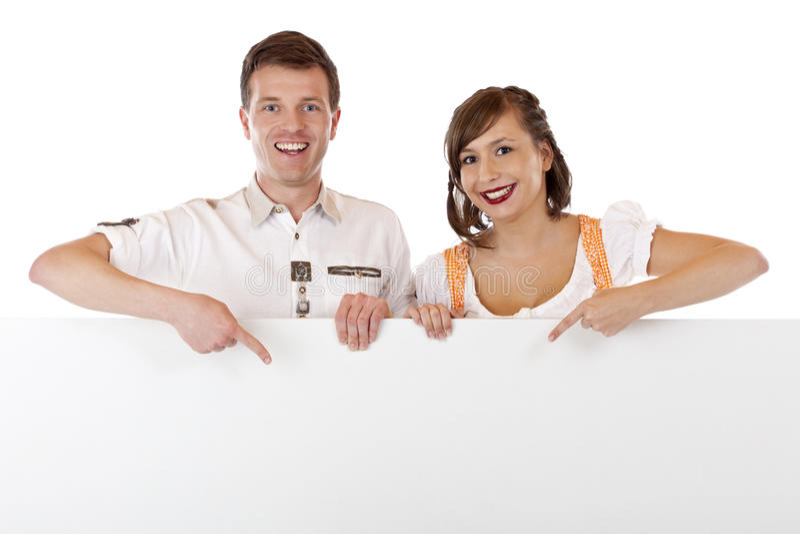 Homem novo e mulher no dirndl que apontam no espaço do anúncio foto de stock royalty free