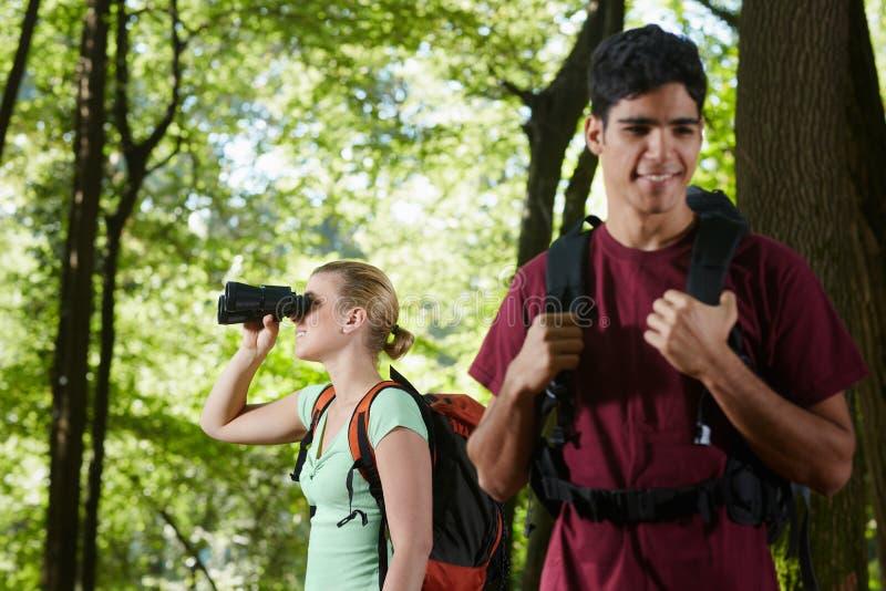 Homem novo e mulher que caminham com binóculos fotografia de stock royalty free