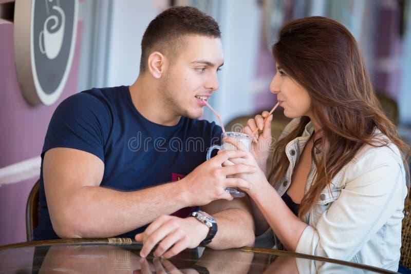 Homem novo e mulher que compartilham da bebida em um café imagem de stock royalty free