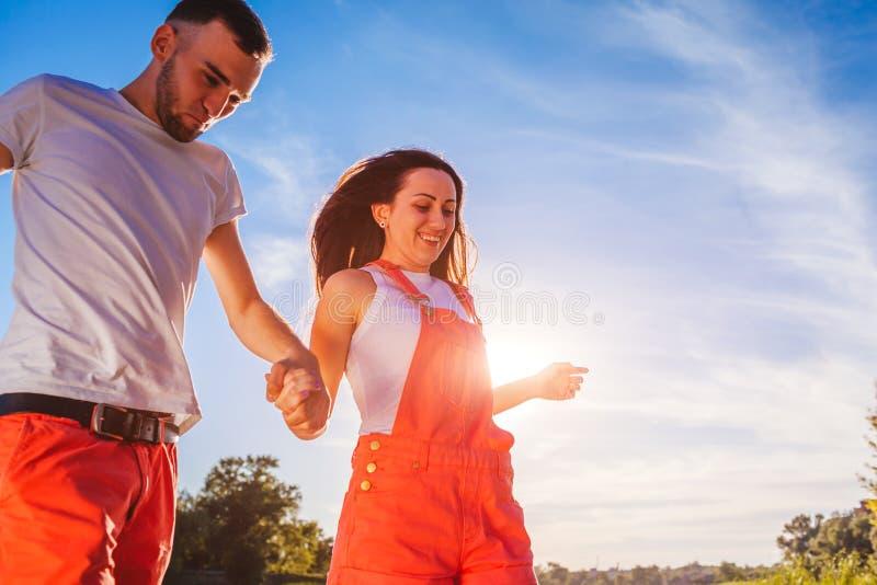Homem novo e mulher que correm no fundo do céu azul Pares que têm o divertimento no por do sol Férias de verão imagens de stock