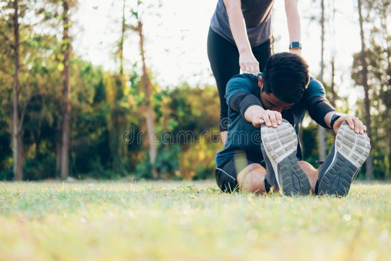 Homem novo e mulher que esticam no parque imagem de stock