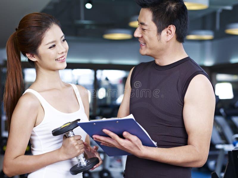 Homem novo e mulher que falam no gym imagens de stock