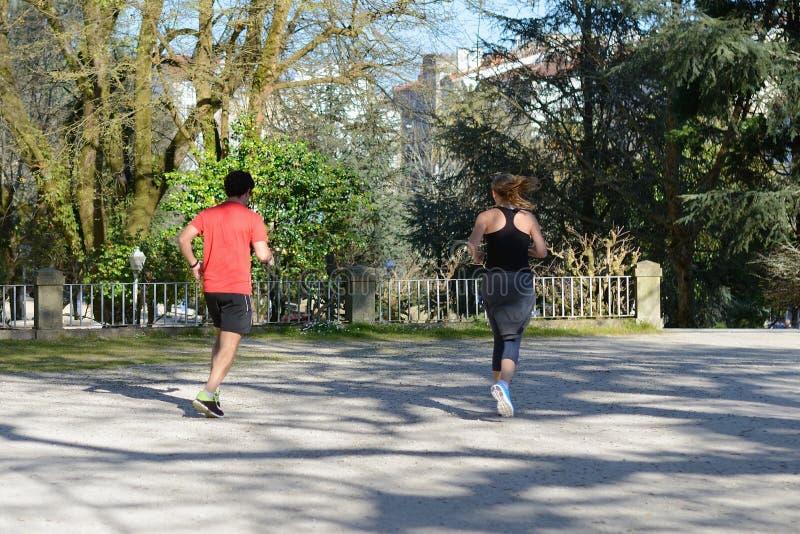 Homem novo e mulher que movimentam-se em um parque da cidade foto de stock