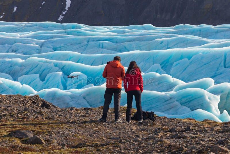 Homem novo e mulher que olham e que navegam um zangão de voo no céu claro azul antes do cenário de nivelamento bonito de Skaftafe fotos de stock royalty free