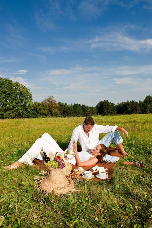 Homem novo e mulher que relaxam no prado foto de stock royalty free