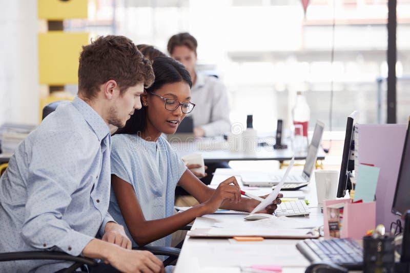 Homem novo e mulher que trabalham junto em um escritório de plano aberto imagem de stock