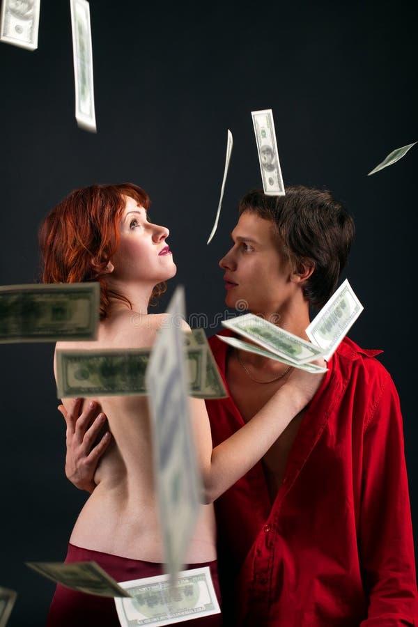 Homem novo e mulher sob a queda do dinheiro fotos de stock royalty free