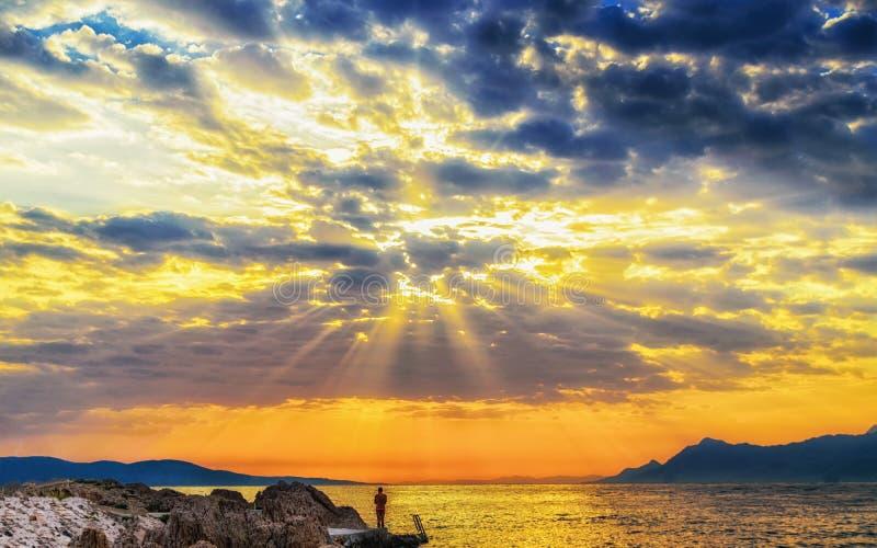 Homem novo e raios celestiais do sol imagem de stock royalty free