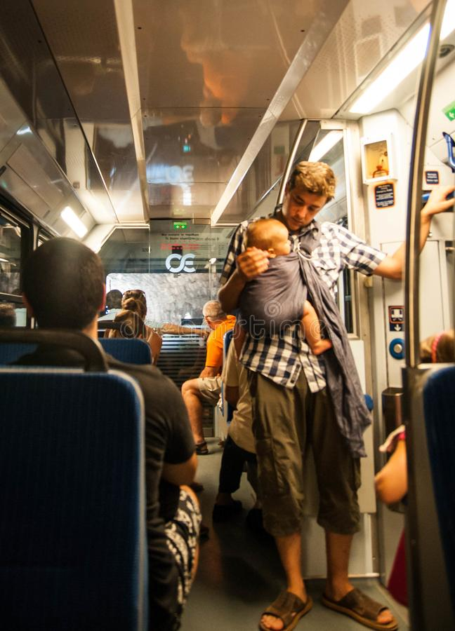 Homem novo e seu bebê pequeno no estilingue na iluminação do por do sol que viaja no carro de trem fotos de stock
