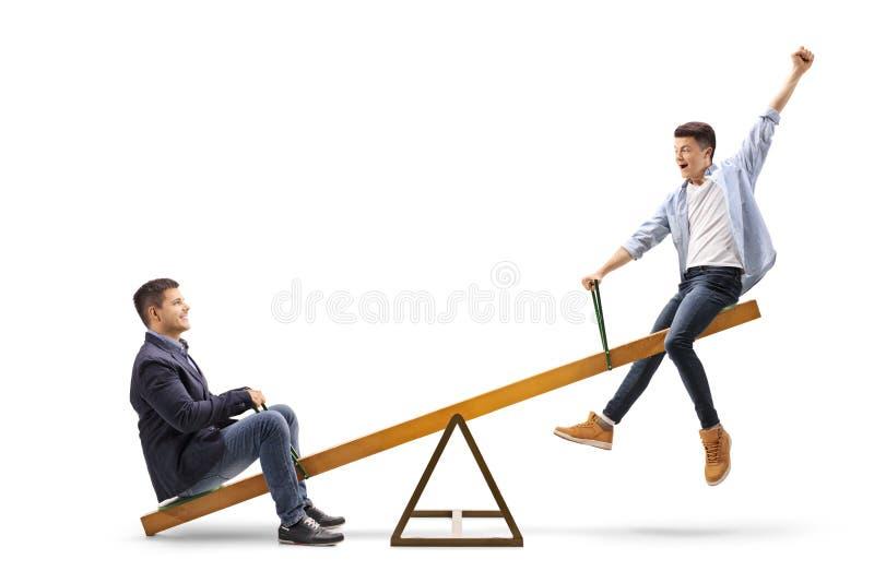 Homem novo e um adolescente em uma balancê foto de stock