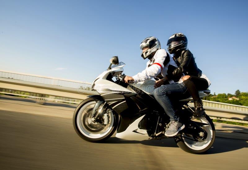 Homem novo e uma mulher em uma motocicleta fotografia de stock