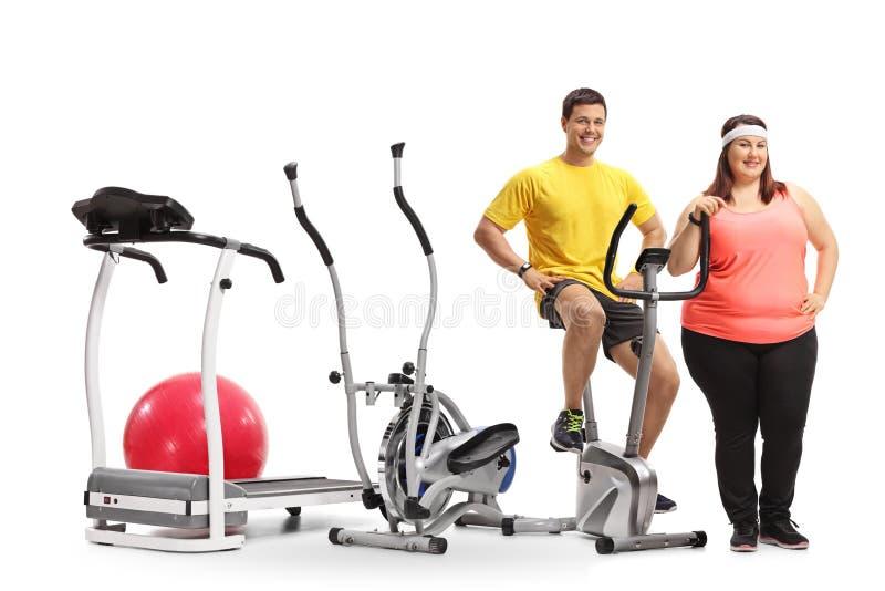 Homem novo e uma mulher excesso de peso com máquinas do exercício imagens de stock