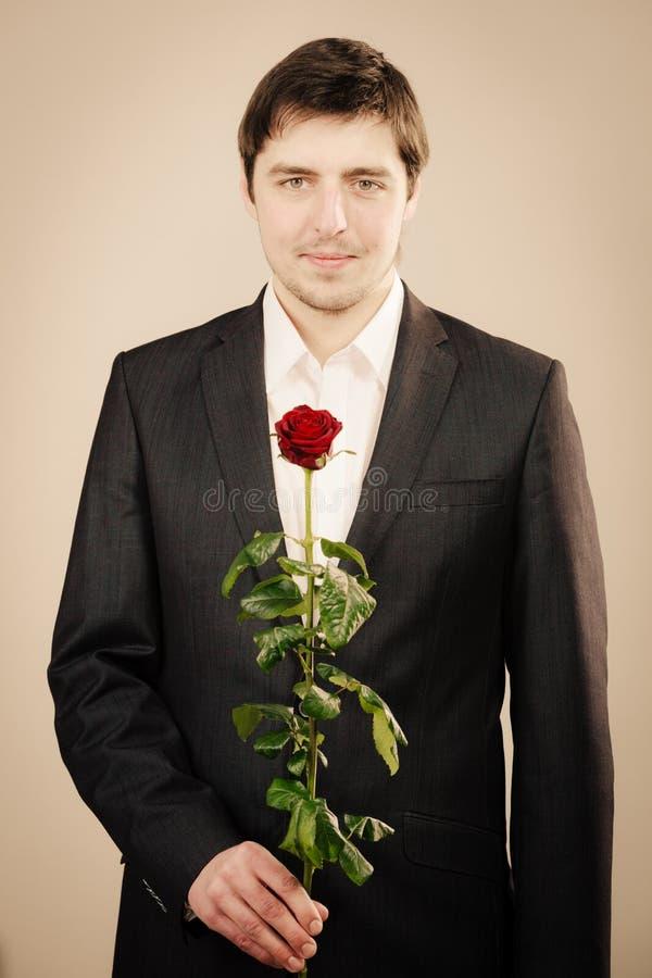 Homem novo elegante com rosa do vermelho fotografia de stock royalty free