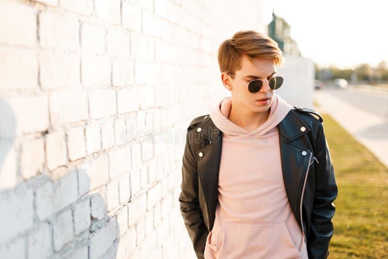 Homem novo elegante considerável do moderno em óculos de sol pretos no casaco de cabedal preto à moda em uma posição cor-de-rosa  fotografia de stock