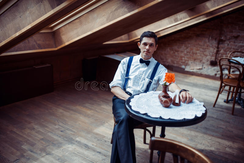 Homem novo elegante nos suspensórios e nos vidros no café imagens de stock royalty free