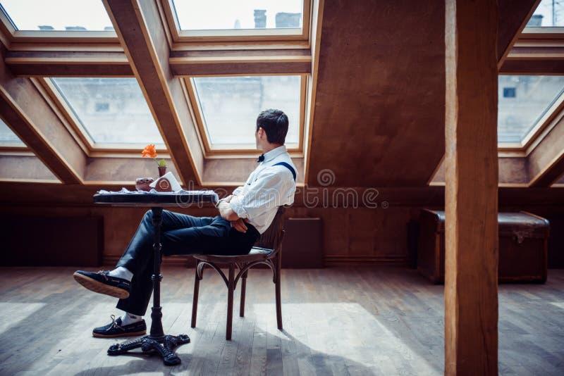 Homem novo elegante nos suspensórios e nos vidros no café foto de stock