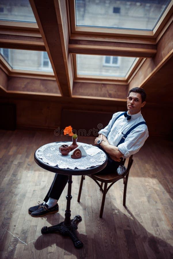 Homem novo elegante nos suspensórios e nos vidros no café fotos de stock