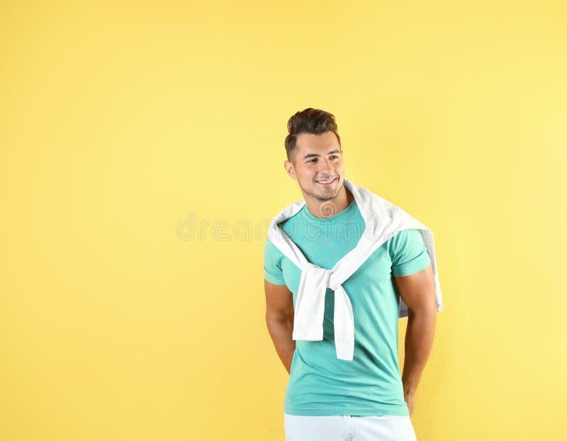 Homem novo em calças de brim à moda no fundo da cor imagens de stock royalty free