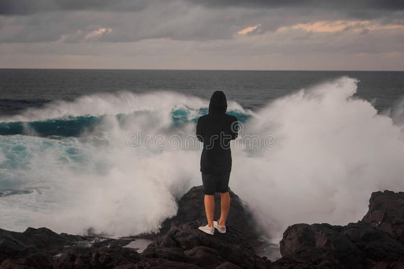 Homem novo em hoody e no short que estão na rocha perto do mar tormentoso imagem de stock