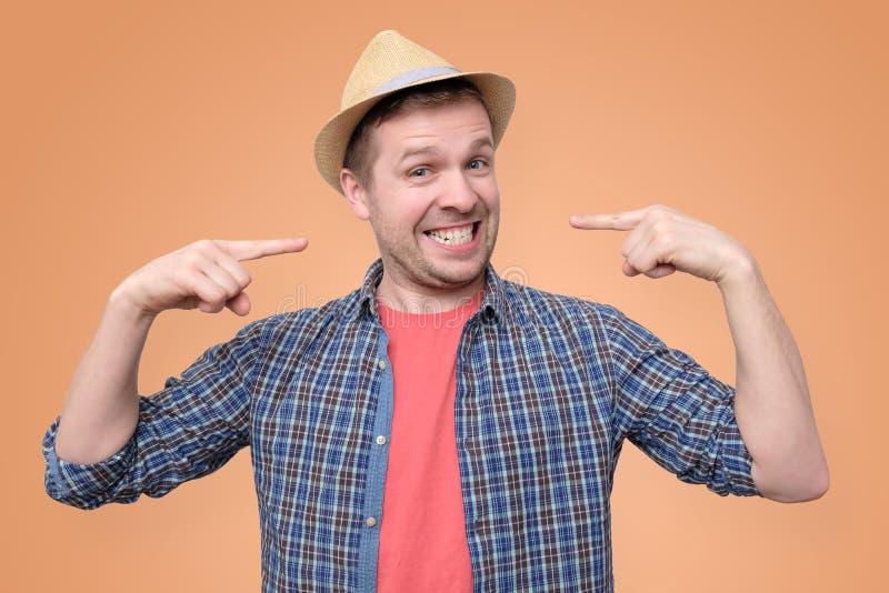 Homem novo em mostras do chapéu do verão em seus dentes imagens de stock royalty free