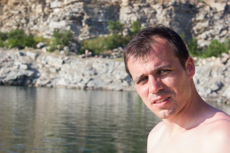 Homem novo em pedras de um fundo, água - mar ensolarado do verão fotos de stock