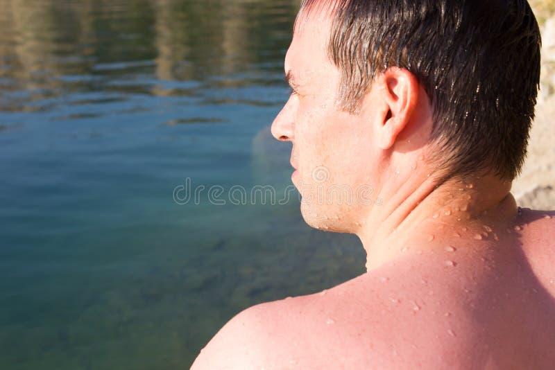 Homem novo em pedras de um fundo, água - mar ensolarado do verão imagem de stock royalty free