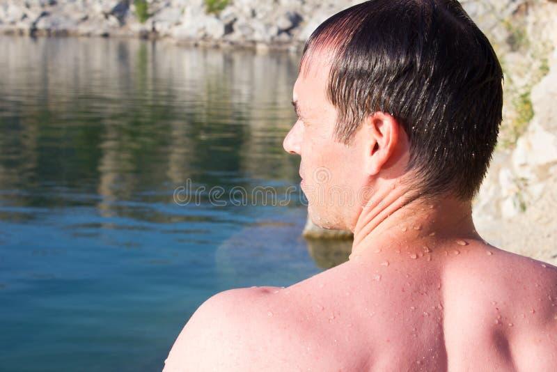 Homem novo em pedras de um fundo, água - mar ensolarado do verão foto de stock