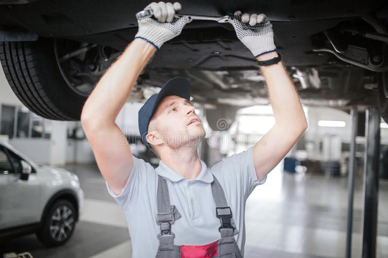 Homem novo em processo do trabalho debaixo do carro Olha acima para endireitar e guardar a chave grande com ambas as mãos É fotografia de stock royalty free