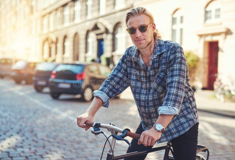 Homem novo em sua bicicleta foto de stock royalty free